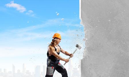 Sterke man in uniforme brekende muur met hamer Stockfoto