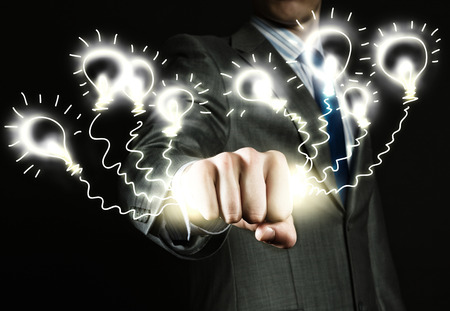 close fist: Close up of businessman grasping light bulbs in fist Stock Photo