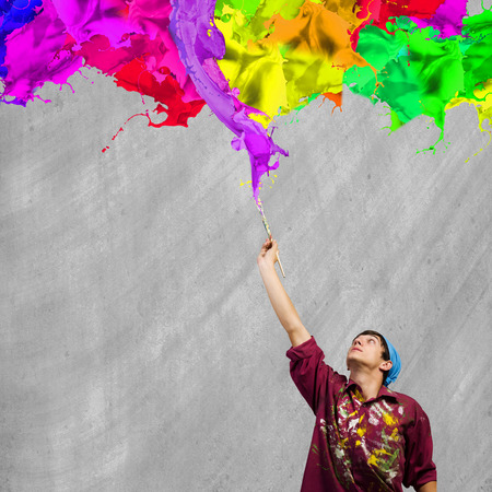 brush in: Young handsome man painter with brush in hand Stock Photo