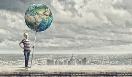 Cute little girl with Earth planet banner. Elements of this image are furnished by NASA photo