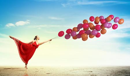 Jeune femme en robe et ballerines dansant avec des ballons colorés