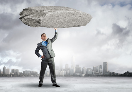 above head: Powerful businessman holding huge stone above head Stock Photo