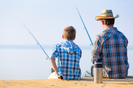 boy and his father fishing together from a pier photo