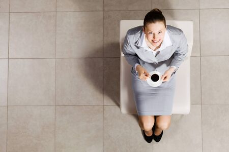 busineswoman: Top view of busineswoman sitting on chair with cup of coffee