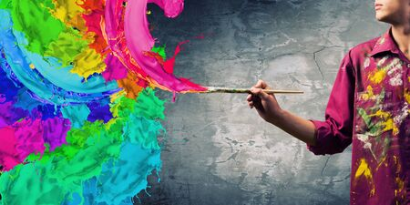 house painter: Young handsome man painter with brush in hand Stock Photo