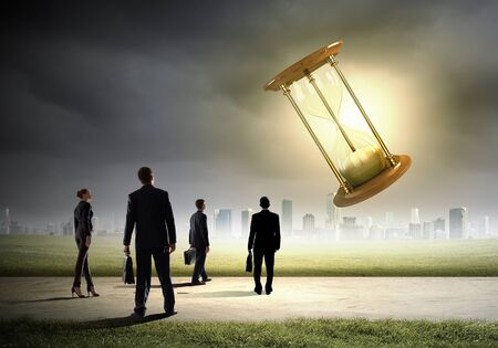hour glass figure: Conceptual image of business people looking at sandglass