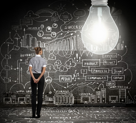 Young businesswoman with bulb and business sketches at background photo