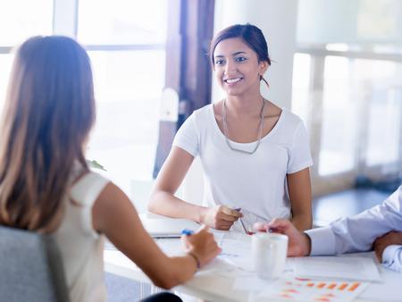 mujer trabajadora: Equipo de tener una discusi�n en la oficina