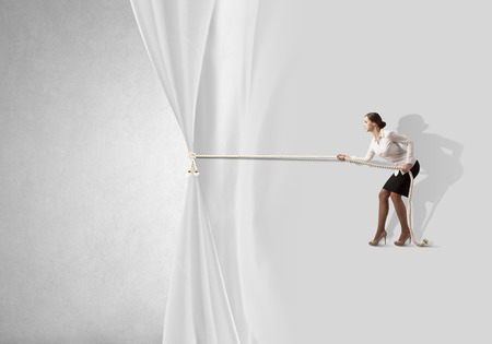 Young businesswoman pulling curtain with rope. Place for text photo