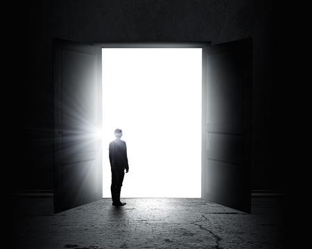 light worker: Rear view of businessman standing in light of opened door Stock Photo