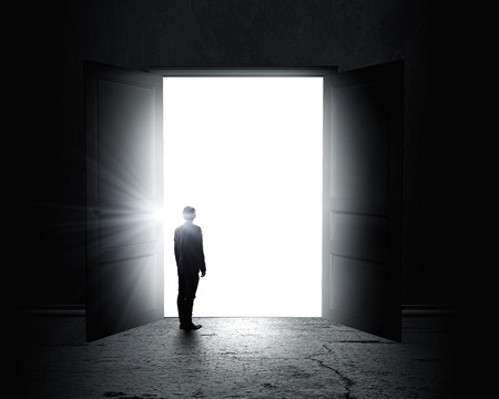 puerta abierta: Vista trasera del hombre de negocios de pie en la luz de la puerta abierta Foto de archivo