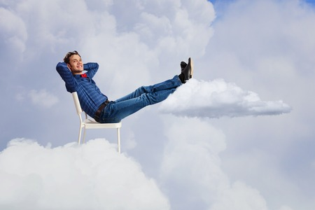 feet up: Young man sitting in chair with legs up and relaxing