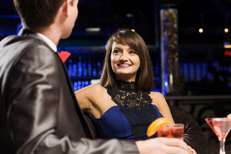 vergezeld: Young handsome man in bar accompanied by elegant lady