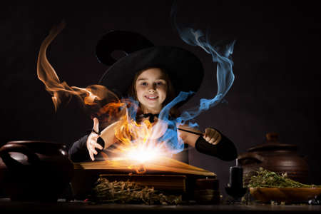 conjure: Little Halloween witch reading conjure from magic book Stock Photo