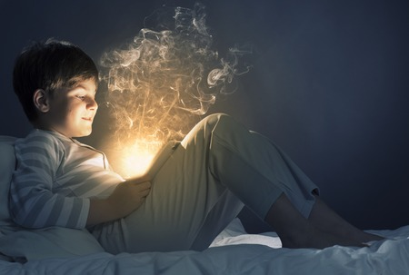 child playing: Cute boy sitting in bed and using tablet pc