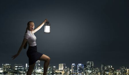 Young businesswoman walking in darkness with lantern in hand photo