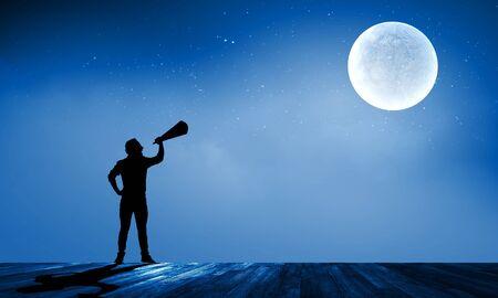 speaking trumpet: Silhouette of man at night screaming in megaphone
