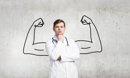 Young male doctor with drawn strong hands behind his back Stock Photo