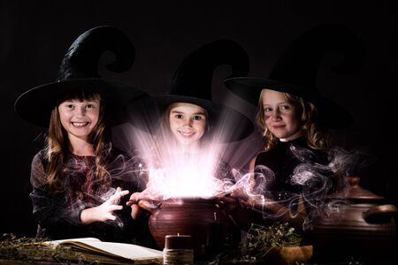 spell: Three little Halloween witches reading spell above pot