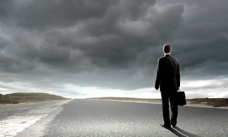 Back view of businessman standing on road and looking far away Stock Photo