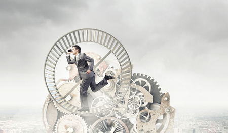 Young businessman in suit running in hamster wheel photo