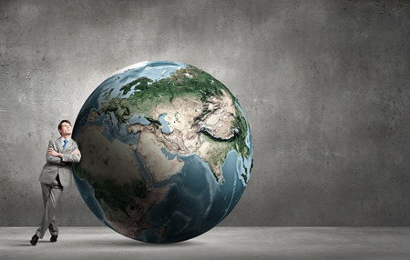 Businessman leaning on huge Earth planet. Elements of this image are furnished by NASA photo