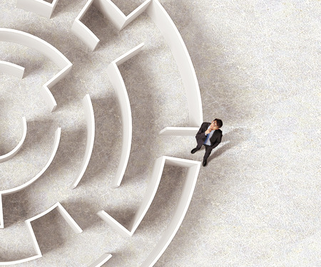 Top view of successful businessman standing near the entrance of labyrinth Stock Photo