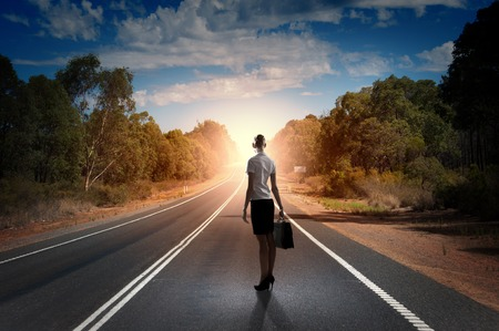 Back view of businesswoman standing on road and looking far away Stock Photo