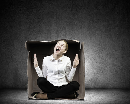 uncomfortable: Young businesswoman sitting in carton box and feeling uncomfortable Stock Photo