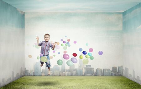 Little cute boy in jump and colorful balloons around photo
