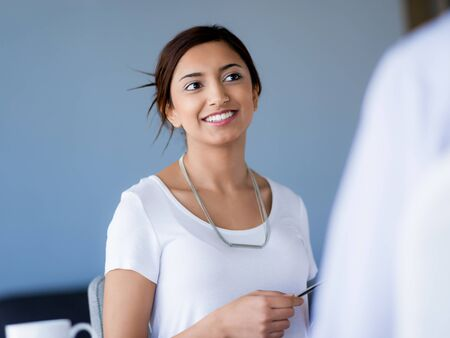 collegue: Young business woman talking to her collegue and smiling