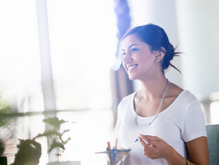 mujer trabajadora: Mujer de negocios joven que habla con su colega y sonriente