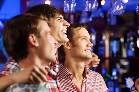 Three young men at bar watching match and shouting photo