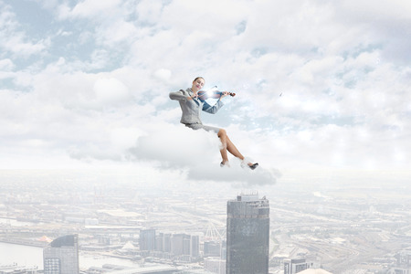 solo violinist: Young businesswoman sitting on cloud and playing violin