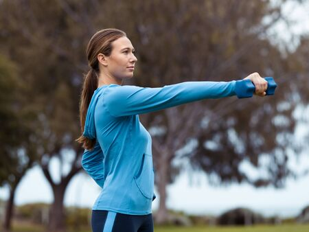activewear: Sporty young woman with dumbbells outdoors