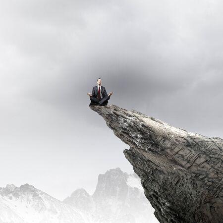 Young businessman sitting lotus pose on edge of rock mountain