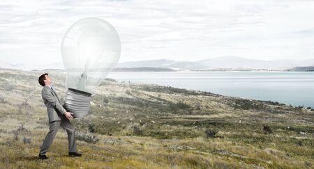 Businessman making effort to carry huge light bulb photo