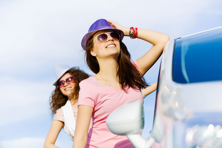 near side: Young pretty women standing near white car at side of road