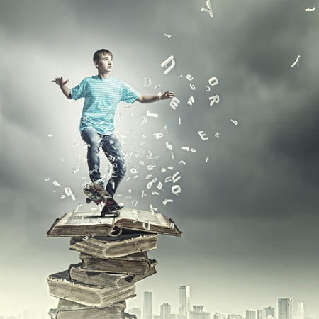 boy skater: Boy skater standing on pile of old books