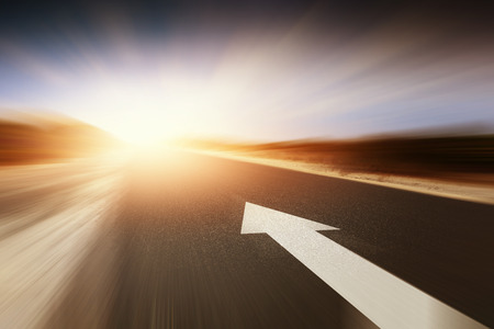 Conceptual image of asphalt road and direction arrow Stock Photo