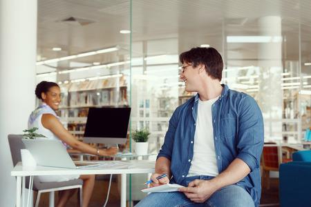 amigas conversando: Tiro de dos colegas que tienen una conversación amable en el mostrador