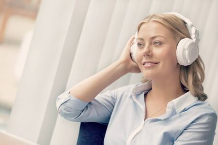 Woman in headphones sitting at desk in office photo