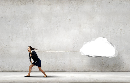 Young businesswoman pulling white cloud with rope photo