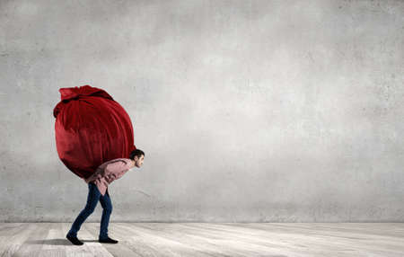 carrying heavy: Young man in casual carrying heavy red bag