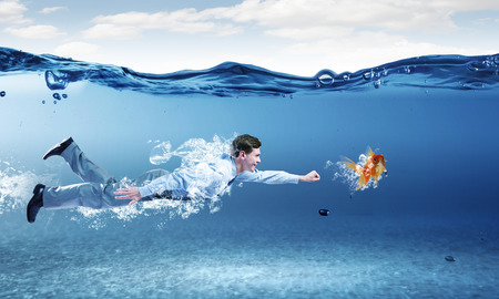 Young businessman in suit swimming under water photo