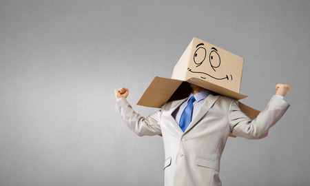 boxy: Businessman wearing carton box with drawn emotions on head Stock Photo