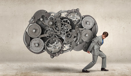 Young businessman carrying huge gears mechanism on back photo