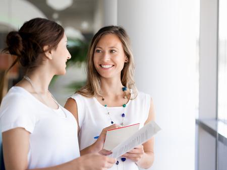 Dos colegas mujeres de pie junto a la otra en una oficina