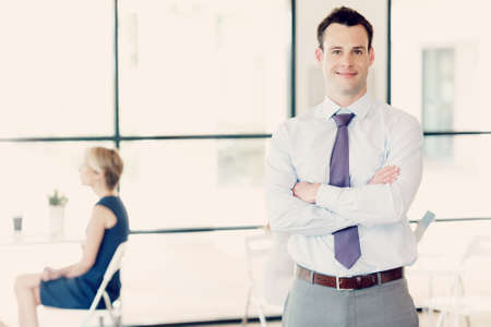 collegue: Young businessman standing in office with her collegue on the background