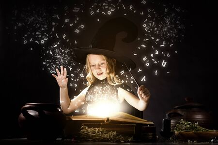Little Halloween witch reading conjure from magic book photo